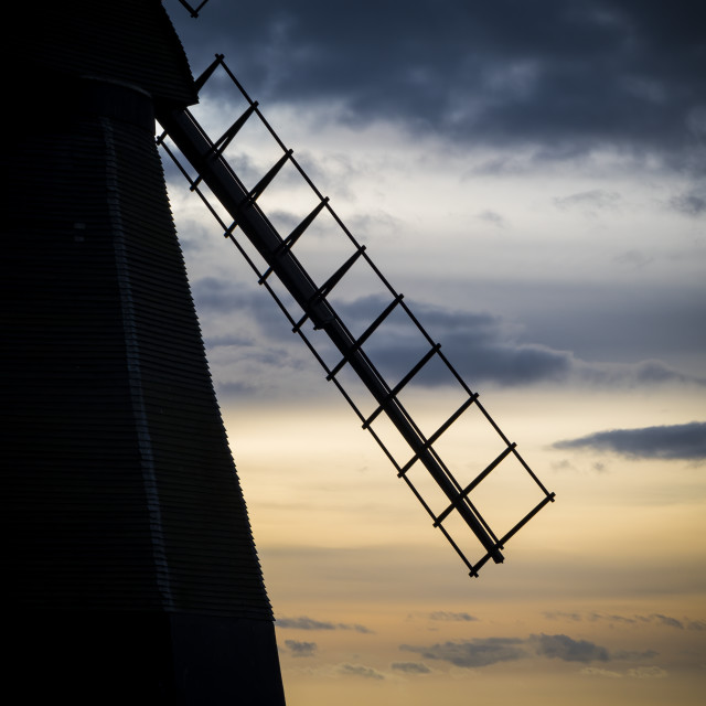 """""""Traditional windmill silhouetted against modern offshore wind farm"""" stock image"""