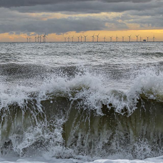 """Waves crashing on windy day near offshore wind farm"" stock image"