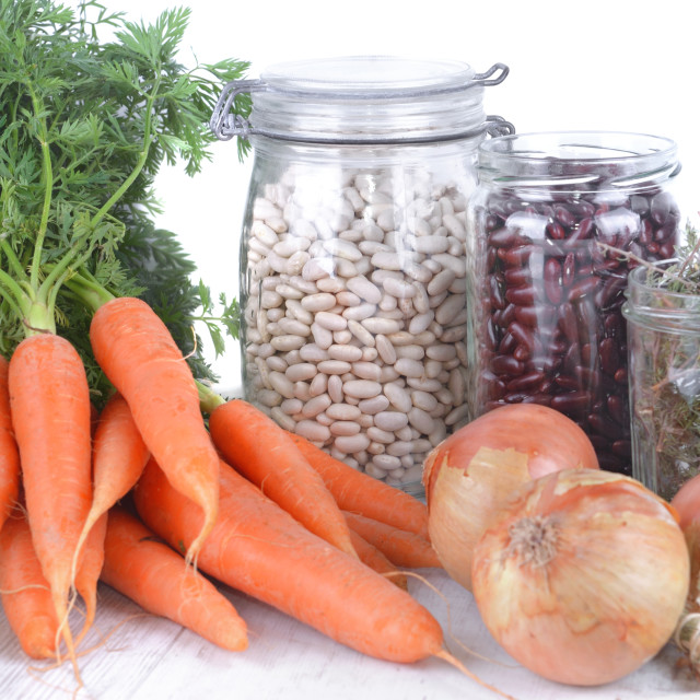 """""""fresh carrots and dry bean in jar with onions and garlic on a table on white background"""" stock image"""