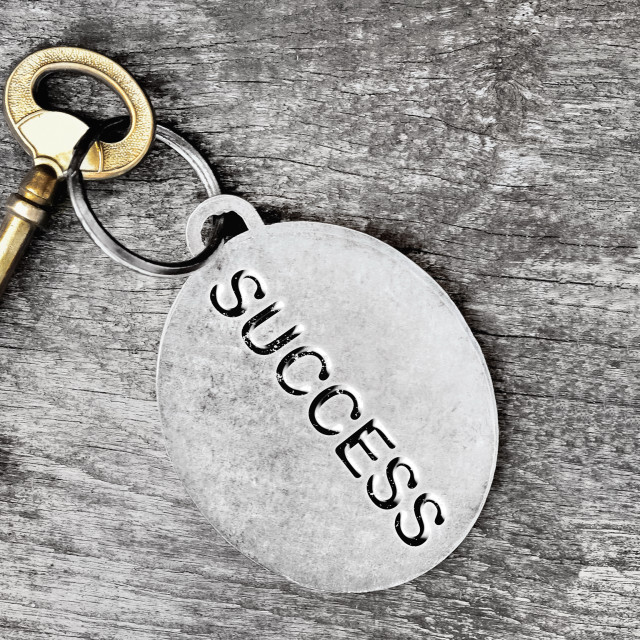"""""""success engraved on a ring of an golden old key on wooden background with other silver"""" stock image"""