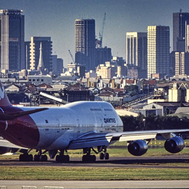 """Qantas Boeing 747 with city"" stock image"