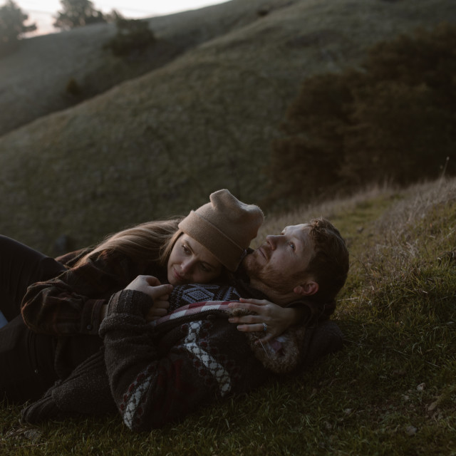 """""""Couple Cuddling in Grass"""" stock image"""