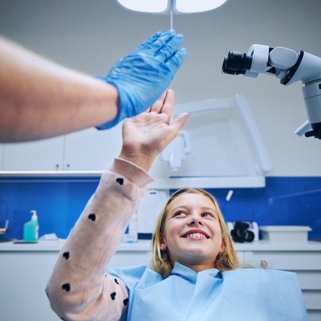 """""""Dentist giving high-five to girl in modern dental surgery"""" stock image"""