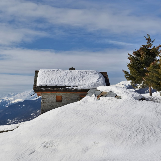 """""""alpine chalet overlooking the valley in snowy mountain"""" stock image"""