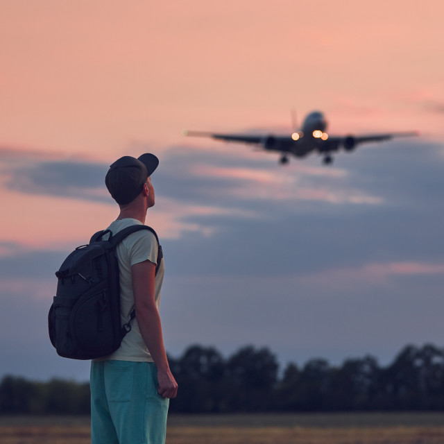 """""""Man looking up at flying airplane"""" stock image"""