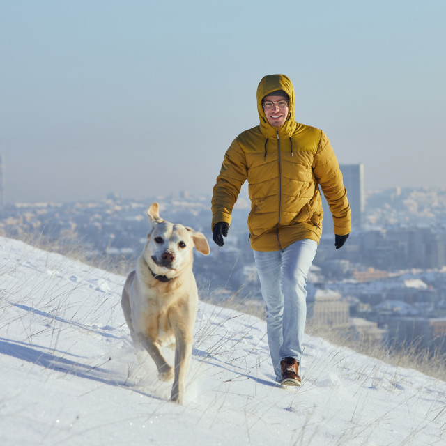 """""""Happy young man with dog in winter"""" stock image"""