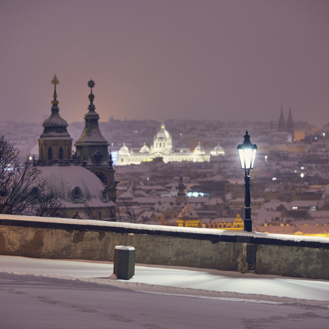"""""""View of illuminated street against snowy city at night"""" stock image"""