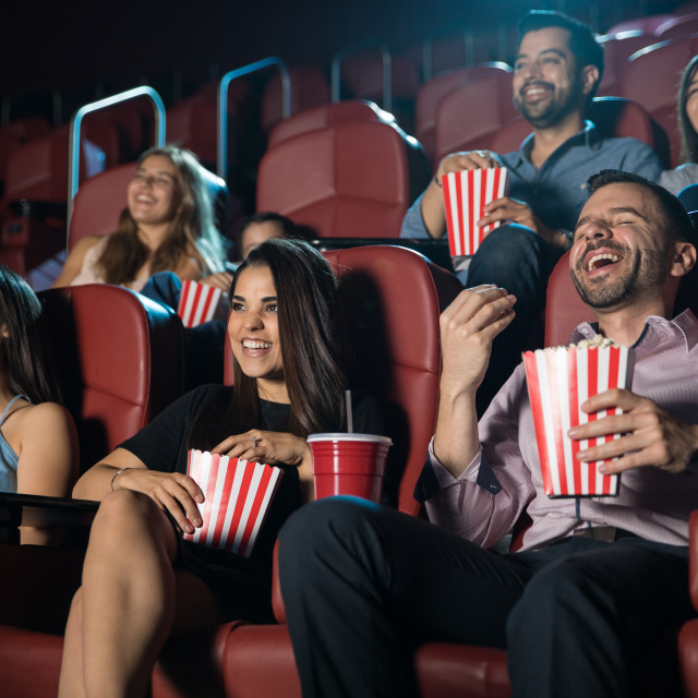 """""""Group of people laughing at the movie theater"""" stock image"""