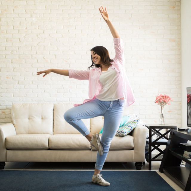 """""""Single woman dancing in the new apartment"""" stock image"""