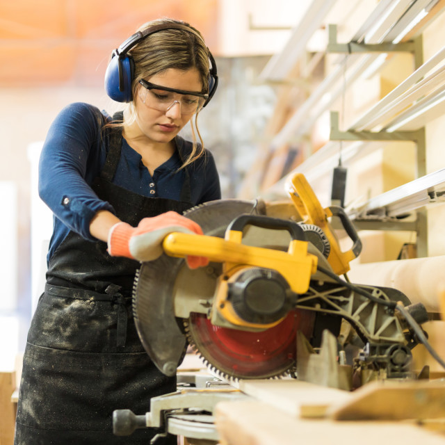 """""""Woman using power tools in a woodshop"""" stock image"""