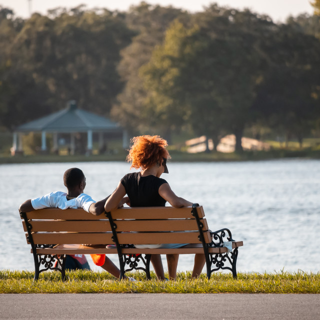 """A YOUNG AFRICAN AMERICAN COUPLE RELAXING ON A PARK BENCH"" stock image"