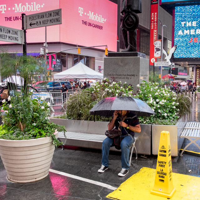 """""""Man on mobile phone under umbrella, Times Square."""" stock image"""