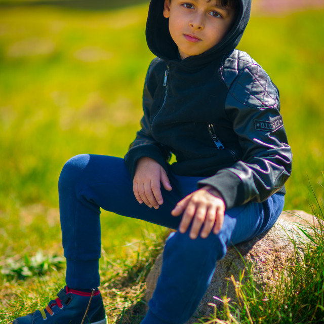 """""""Young boy sitting on a stone, posing for camera"""" stock image"""