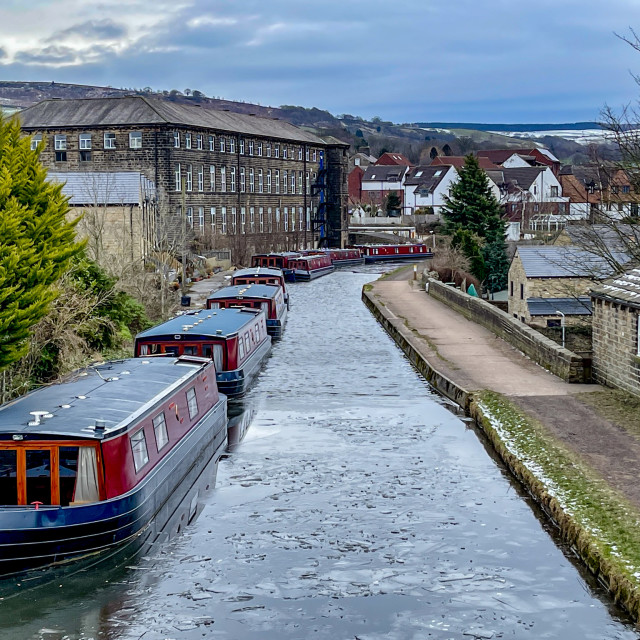 """""""Holiday Narrowboat/Barge Moored on the Leeds and Liverpool Canal at Silsden (Cobbydale) Yorkshire, England, Photographed 14th February 2021. Industrial Mill in background."""" stock image"""