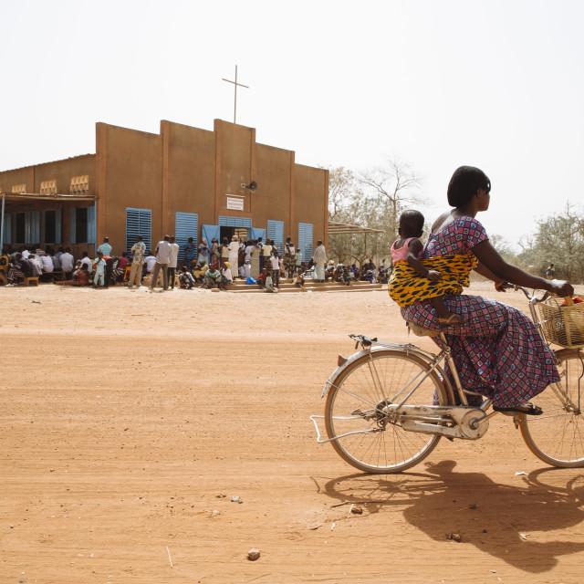 """""""Catholic Mass on Sunday in Burkina Faso, Woman on bicycle"""" stock image"""