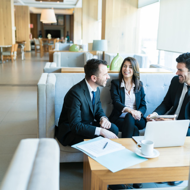 """""""Mid Adult Professionals Sharing A Light Moment In Lobby"""" stock image"""