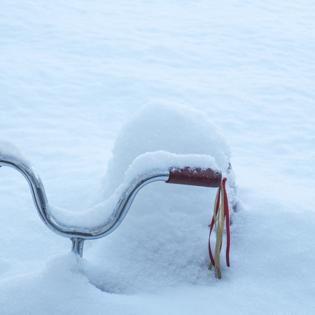 """""""Red tricycle with streamers buried in deep snow"""" stock image"""