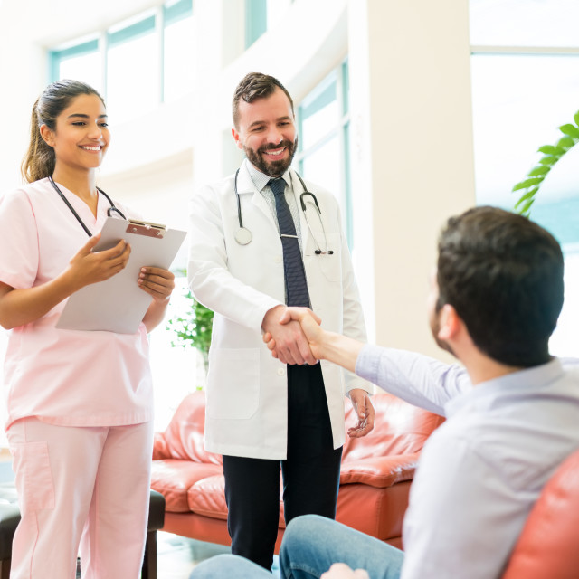 """""""Healthcare Workers Greeting Man Waiting At Hospital"""" stock image"""