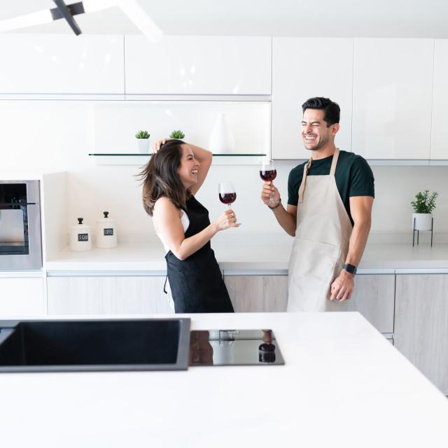 """Happy Couple Enjoying Wine At Home"" stock image"