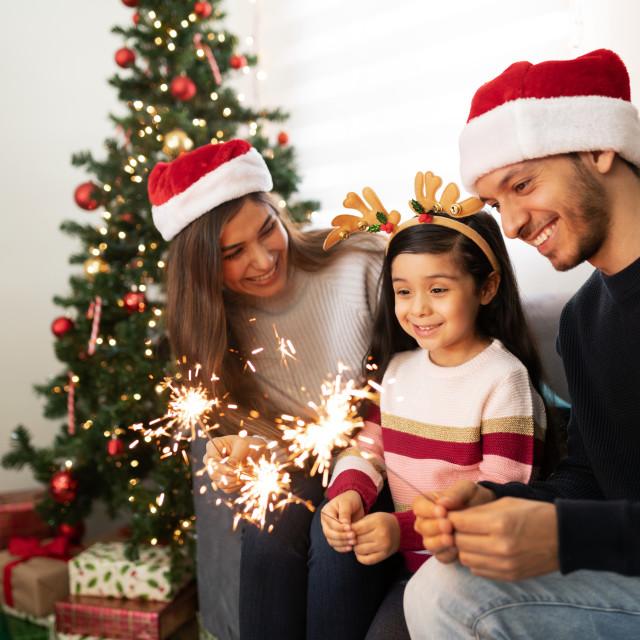 """Hispanic family lighting sparklers at home"" stock image"