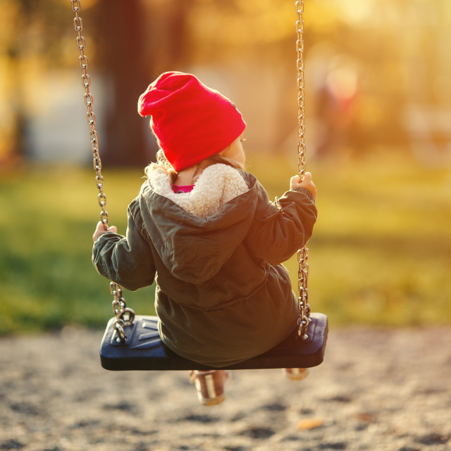 """""""child on a swing in a red cap, fall and spring"""" stock image"""
