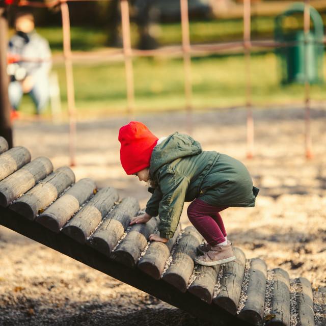 """baby girl on playground, fall"" stock image"