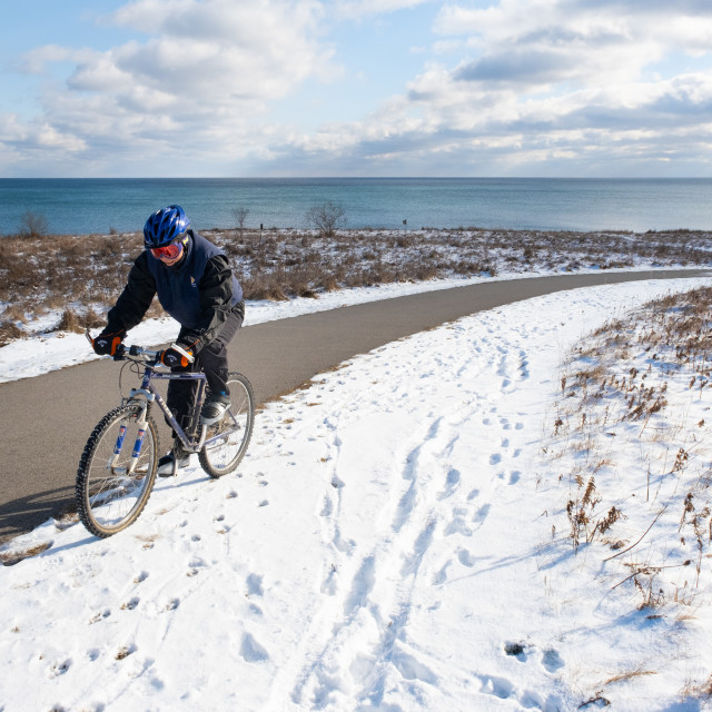 """Dedicated Cyclist Riding Up Snowy Hill"" stock image"