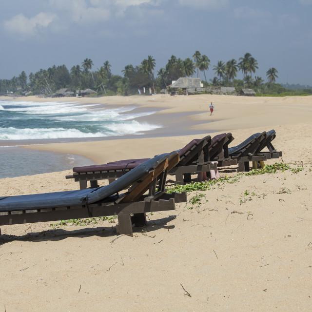 """Wooden sunbeds on beach"" stock image"