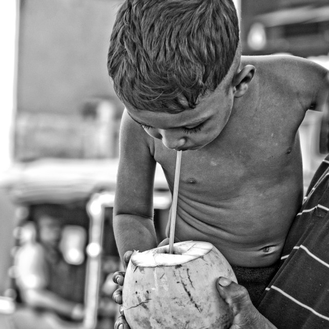 """""""Boy drinking from a coconut"""" stock image"""