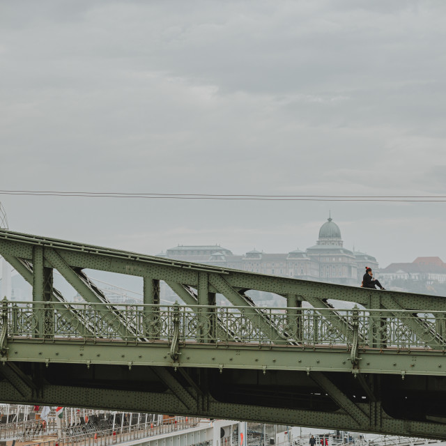 """Sitting and smoking girl on the top of the green Liberty bridge above the Danube river in Budapest"" stock image"