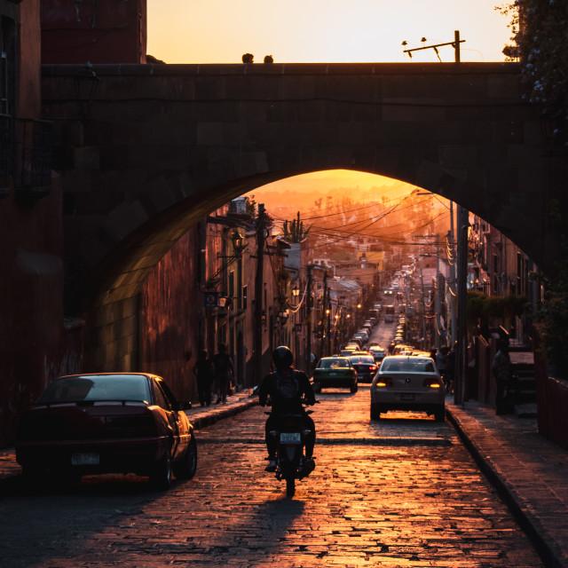 """""""A motorcyclist drives through San Miguel de Allende, Mexico"""" stock image"""
