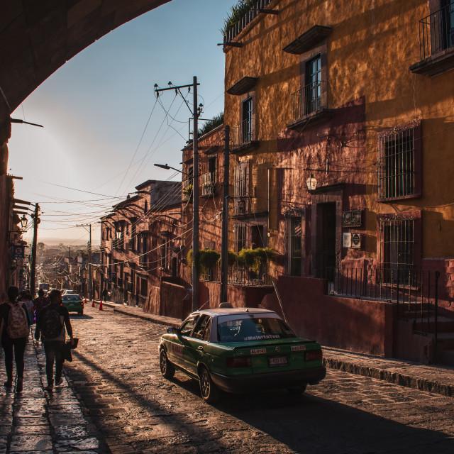 """A Taxi Drives Through San Miguel de Allende, Mexico at Sunset"" stock image"