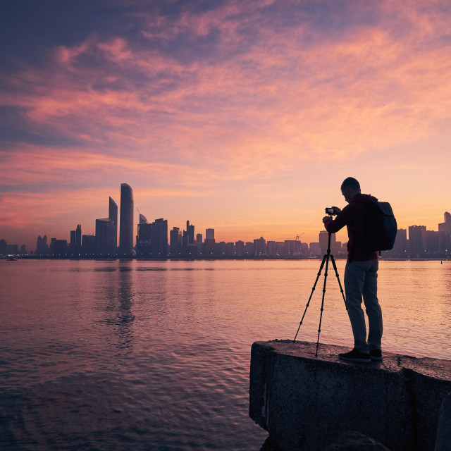 """""""Silhouette of photographer with tripod against urban skyline"""" stock image"""