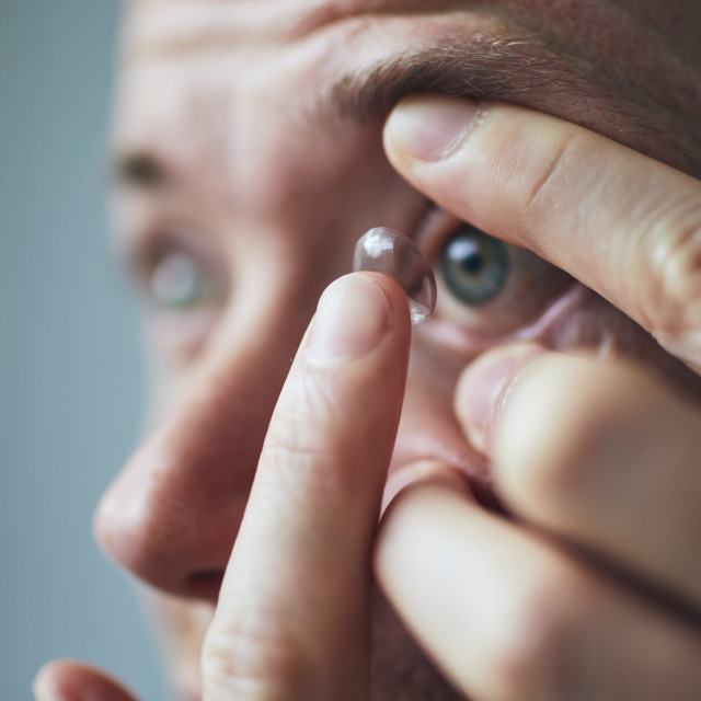"""""""Young man putting contact lens on eye"""" stock image"""
