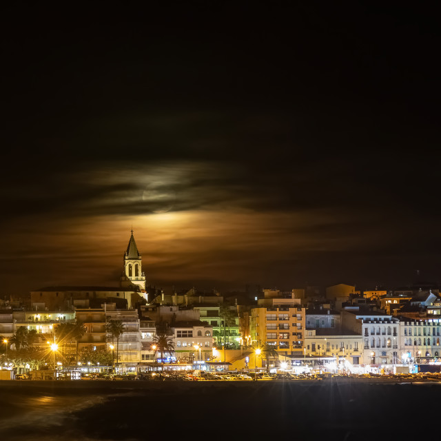 """Night shot with full moon behind the clouds,town Palamos in Span"" stock image"