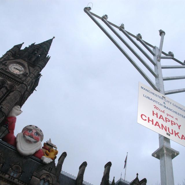 """Inflatable Santa looks down on Menorah"" stock image"