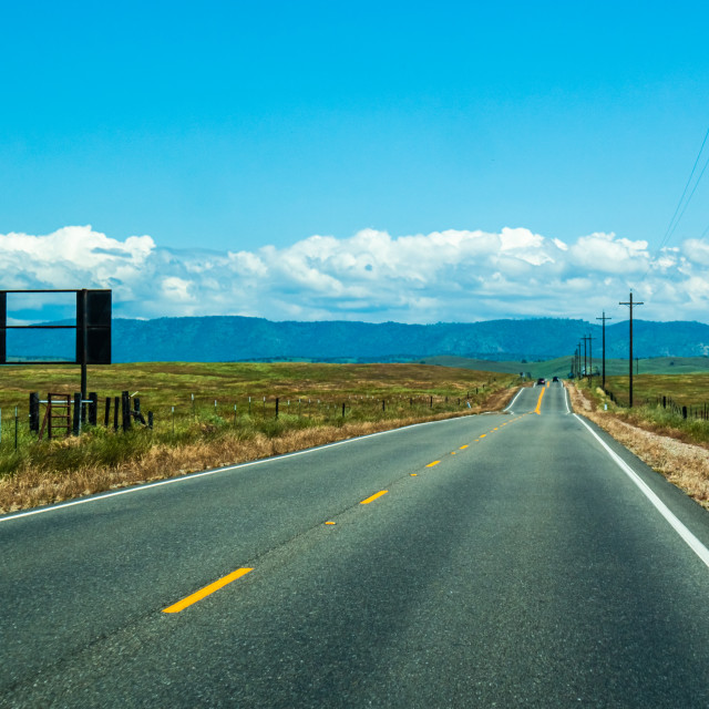 """A long open road ahead looking toward a vanishing point with hills in the far distance"" stock image"