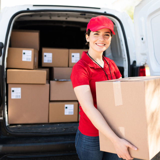 """""""Female courier and driver carrying a bunch of packages"""" stock image"""
