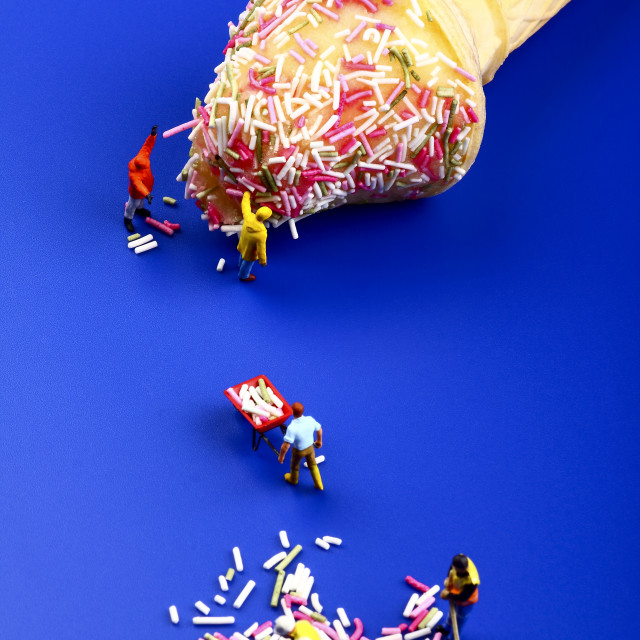 """""""Miniature figure people topping an ice cream cone with hundreds and thousands"""" stock image"""