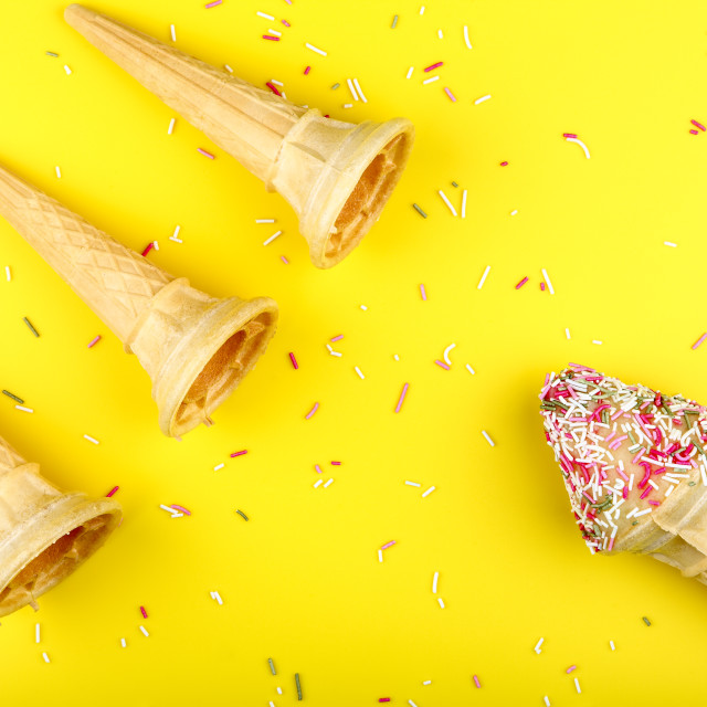 """""""Ice cream cones with hundreds and thousands on a bright yellow background"""" stock image"""