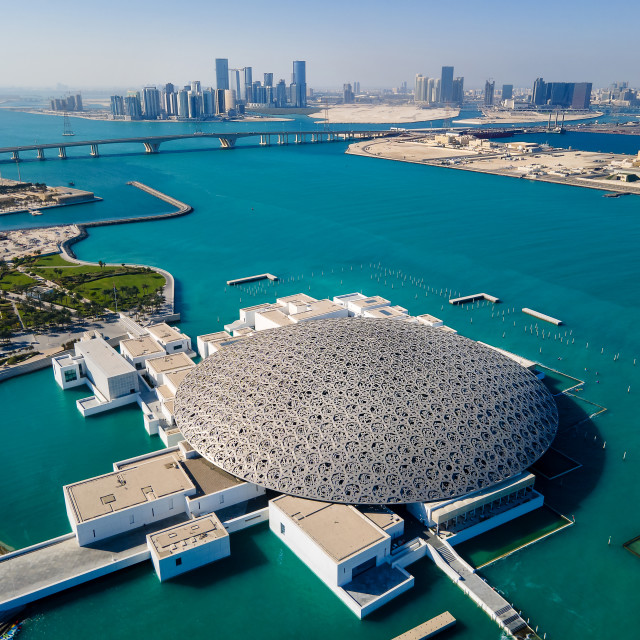 """""""Louvre museum and Abu Dhabi aerial cityscape rising from the seaside water at the United Arab Emirates capital at sunrise"""" stock image"""