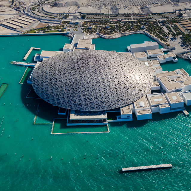 """""""Panoramic aerial view of Louvre museum in Abu Dhabi emirate of the United Arab Emirates at sunrise. View of the building appear to float on the seaside"""" stock image"""