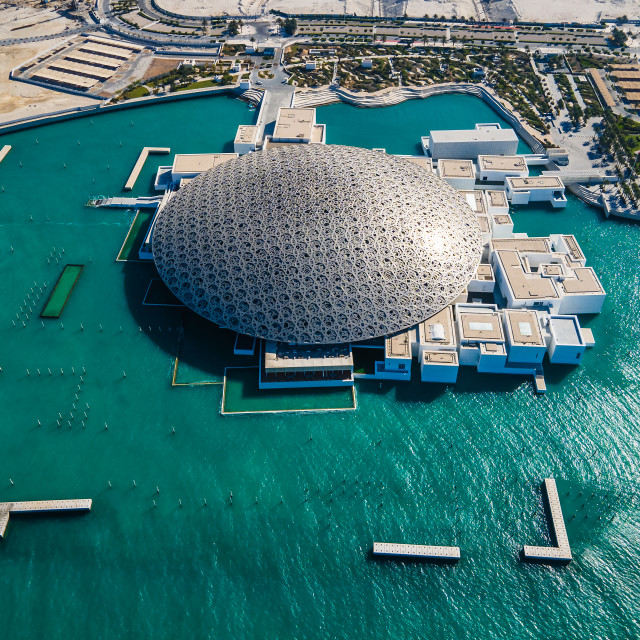 """""""Top view of Louvre museum in Abu Dhabi emirate of the United Arab Emirates at sunrise aerial drone view of the building appear to float on the seaside"""" stock image"""
