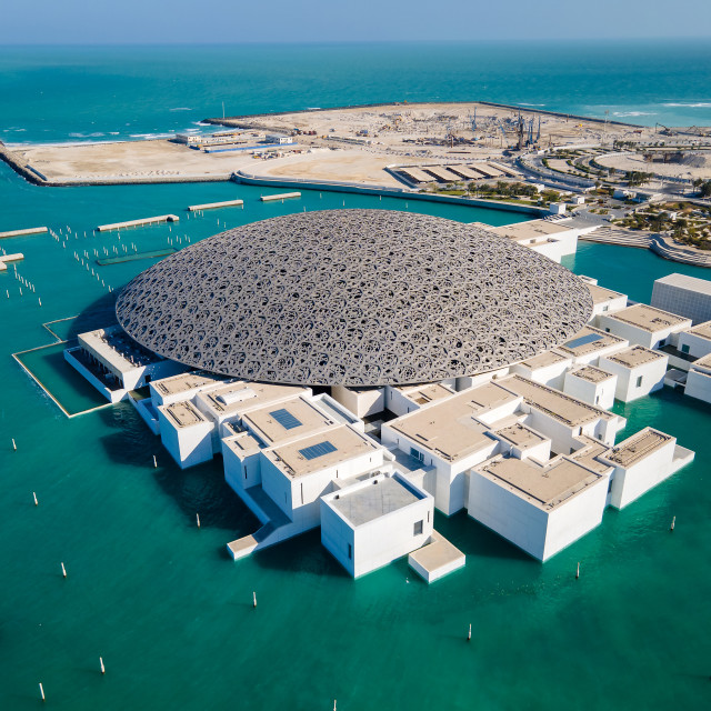 """""""Louvre museum in Abu Dhabi emirate of the United Arab Emirates at sunrise aerial drone view of the building appear to float on the seaside"""" stock image"""