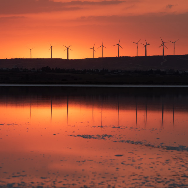 """""""Sunset at the lake and wind turbines for alternative energy at the slope of the hill."""" stock image"""