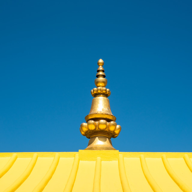"""""""Yellow roof top of a Hindu temple against blue sky."""" stock image"""