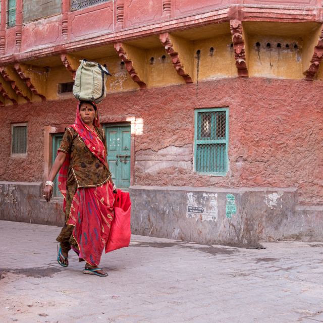 """""""Woman carrying groceries on her head in the streets of the blue city of Jodhpur in Rajasthan, India"""" stock image"""