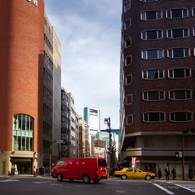 """""""Japanese Postal Van and Taxi Crossing an Intersection in Tokyo"""" stock image"""