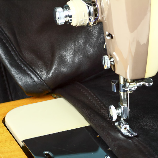 """""""Close up of a vintage sewing machine and leather garment being repaired"""" stock image"""