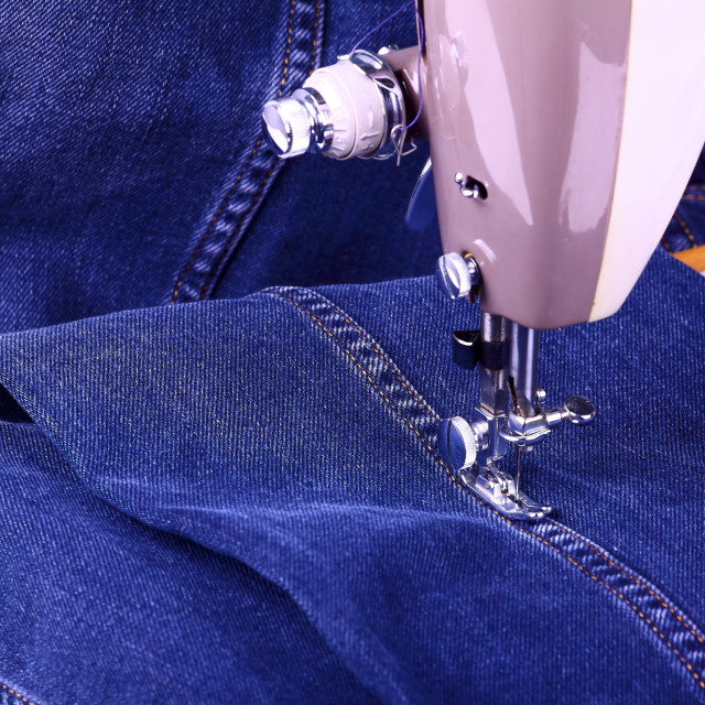 """""""Old vintage sewing machine with blue denim cotton material"""" stock image"""